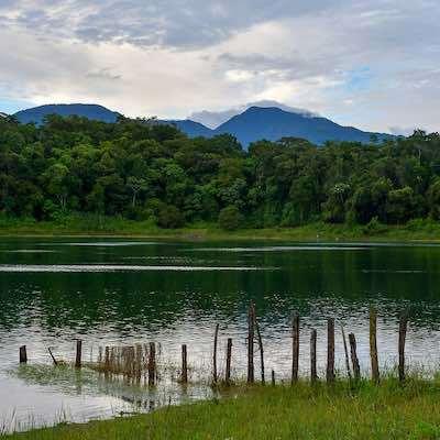 Laguna con cerca y montañas en fondo con cielo nublado